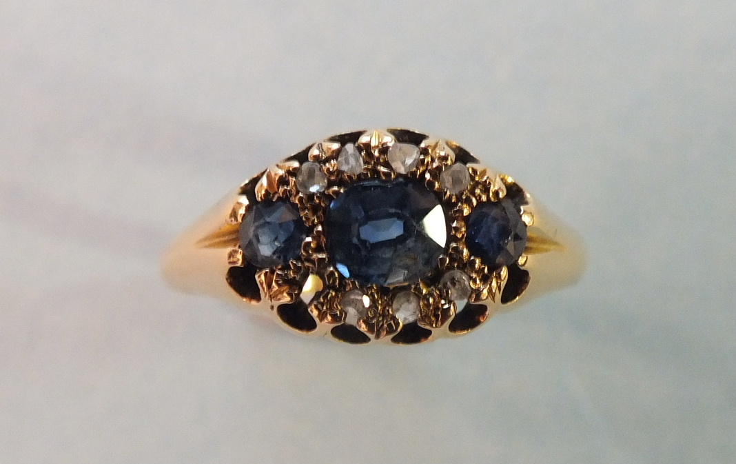 Lot 220 - An Edwardian 18ct gold ring set three sapphires and seven rose cut diamonds, (one setting vacant)