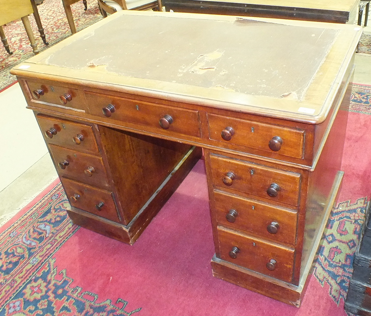 Lot 82 - A late Victorian mahogany knee-hole pedestal writing desk fitted with three frieze drawers and six