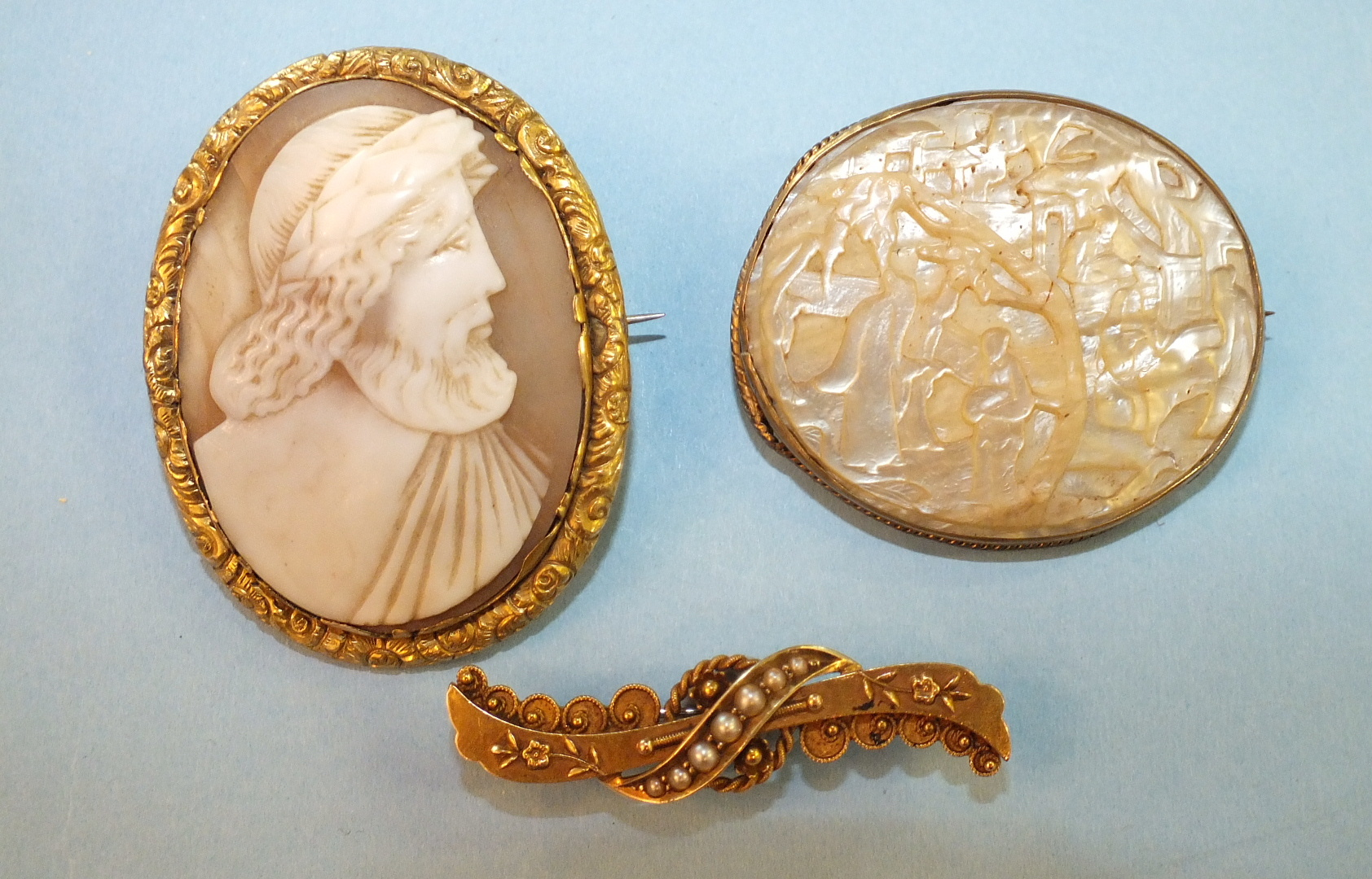 Lot 173 - A Chinese mother-of-pearl brooch carved with figures and a tree, in yellow metal mount, a shell