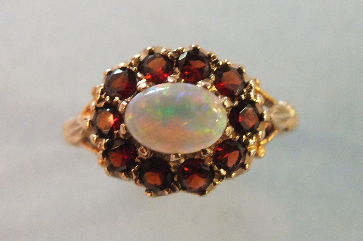 Lot 185 - A garnet and opal cluster ring set ten round-cut garnets around an oval opal, in 9ct gold mount,