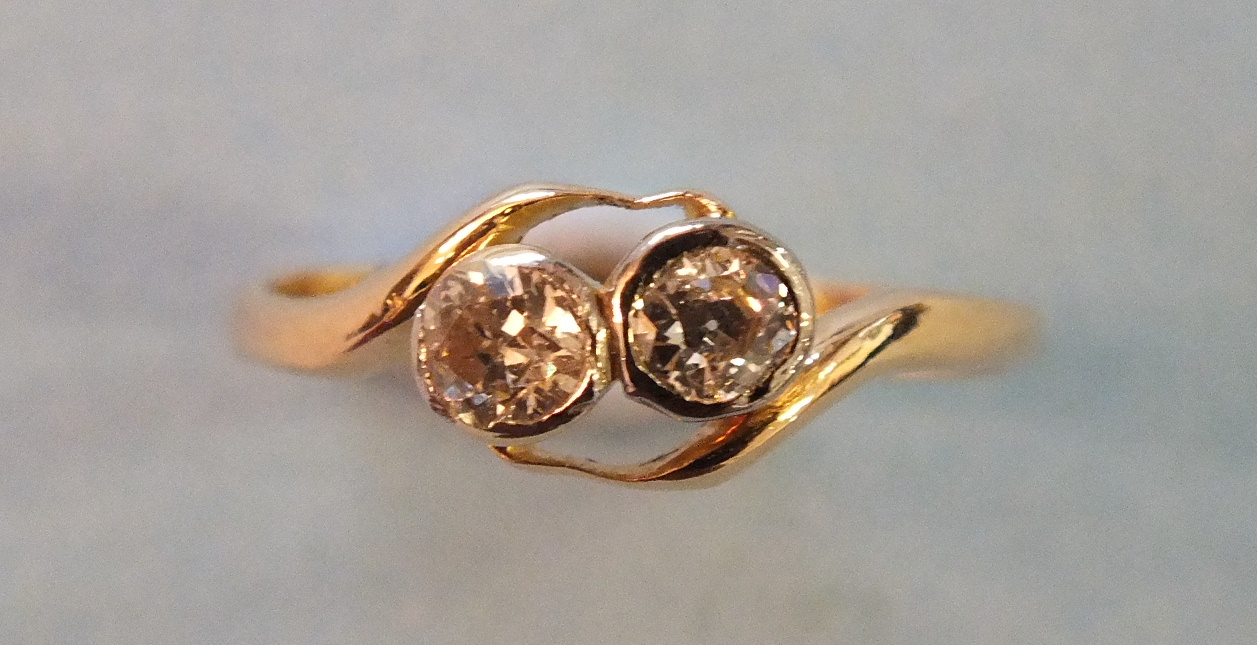 Lot 187 - A two-stone diamond cross-over ring in unmarked yellow gold mount, size M, 2.1g.