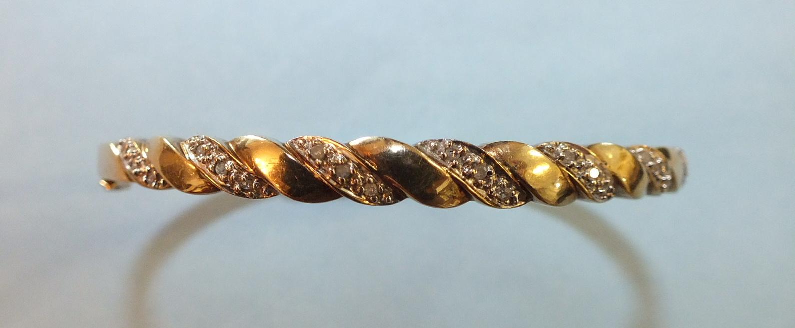 Lot 218 - A 9ct gold hinged bangle of rope-twist design set 8/8-cut diamond points, 9g.