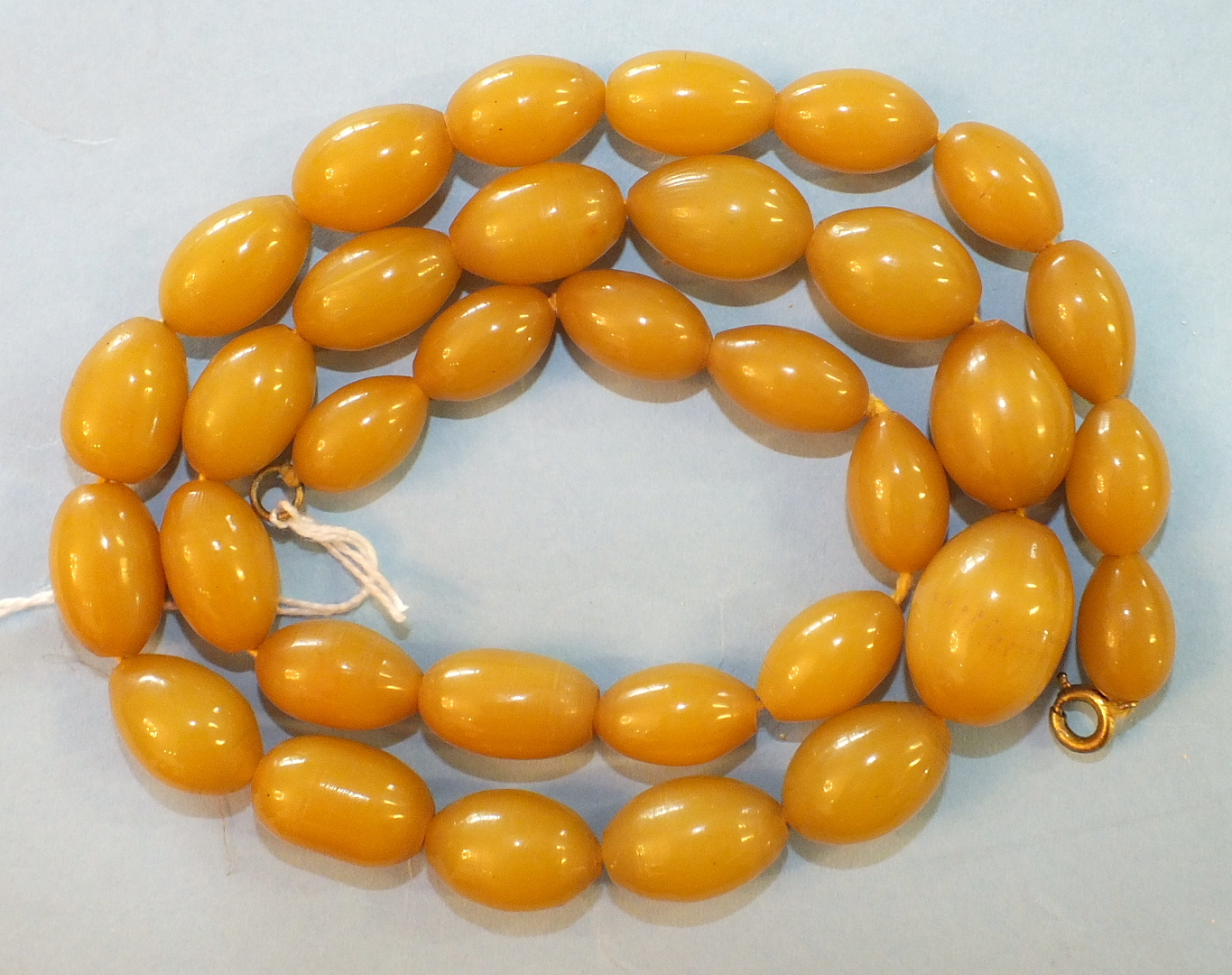 Lot 163 - A string of yellow amber-type Bakelite graduated beads.