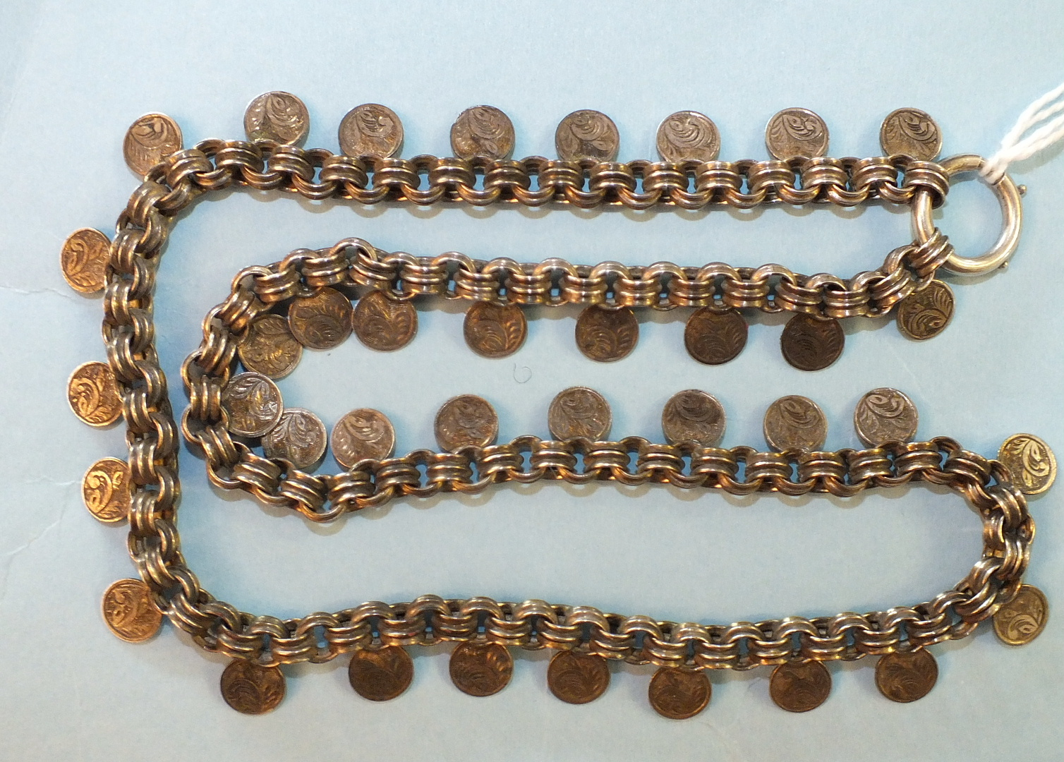 Lot 164 - A Victorian unmarked silver necklace of ribbed links and small engraved discs, with bolt-ring