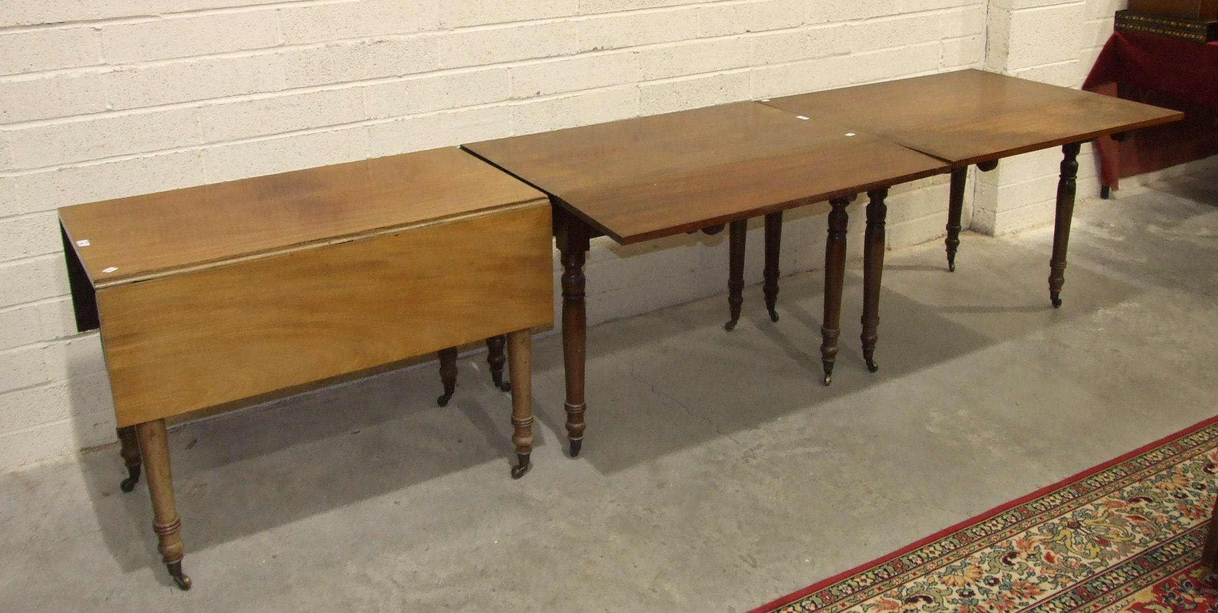 Lot 48 - Three 19th century mahogany drop-leaf tables on turned legs, forming a dining table, each section