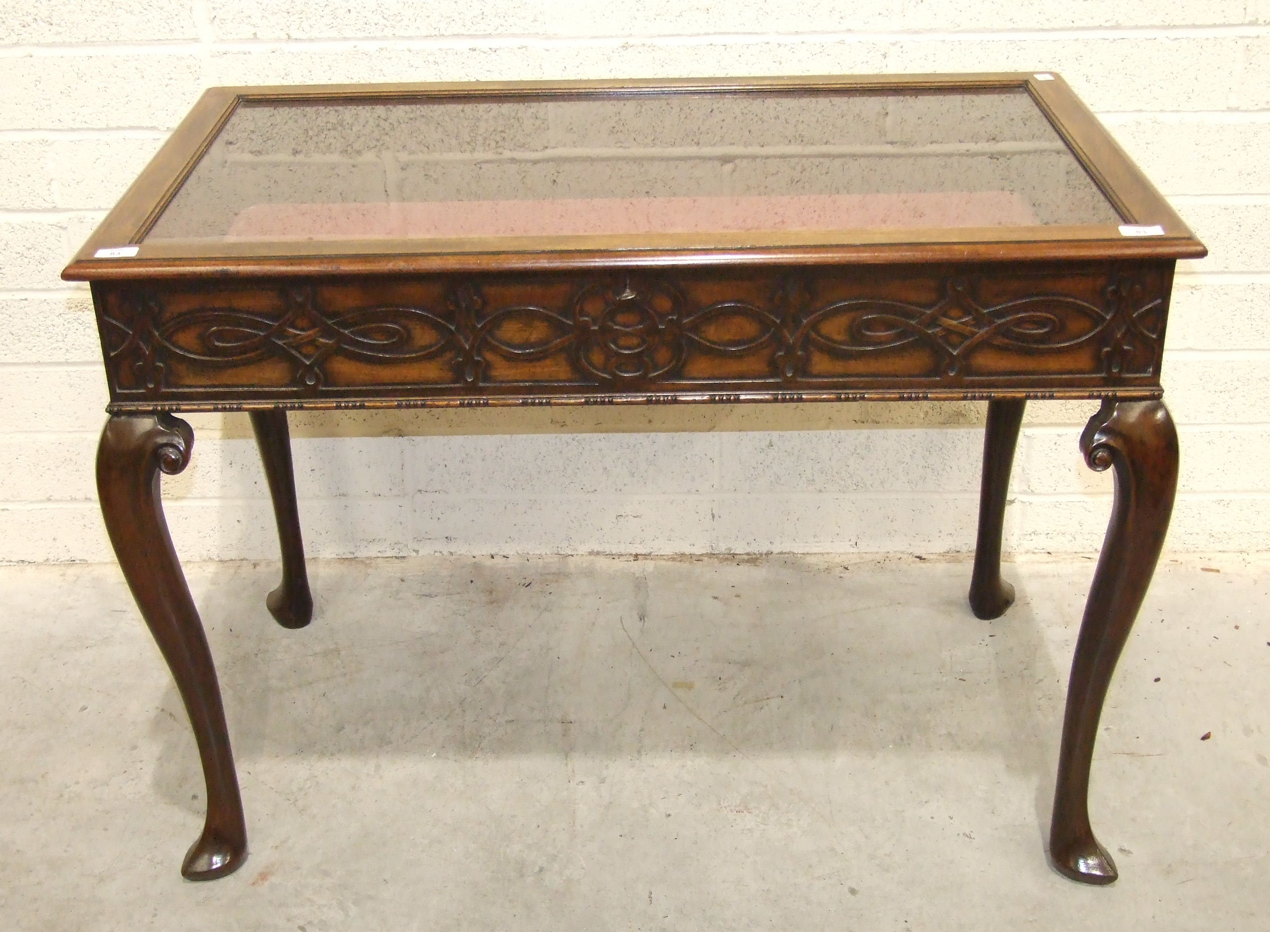 Lot 83 - A 20th century mahogany display table, the glazed top with blind fret frieze on cabriole legs, 105