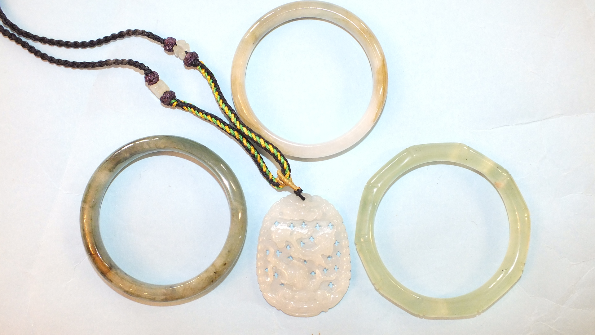 Lot 184 - A modern carved jade pendant on braid necklace and three Chinese jade bangles, (interior diameter