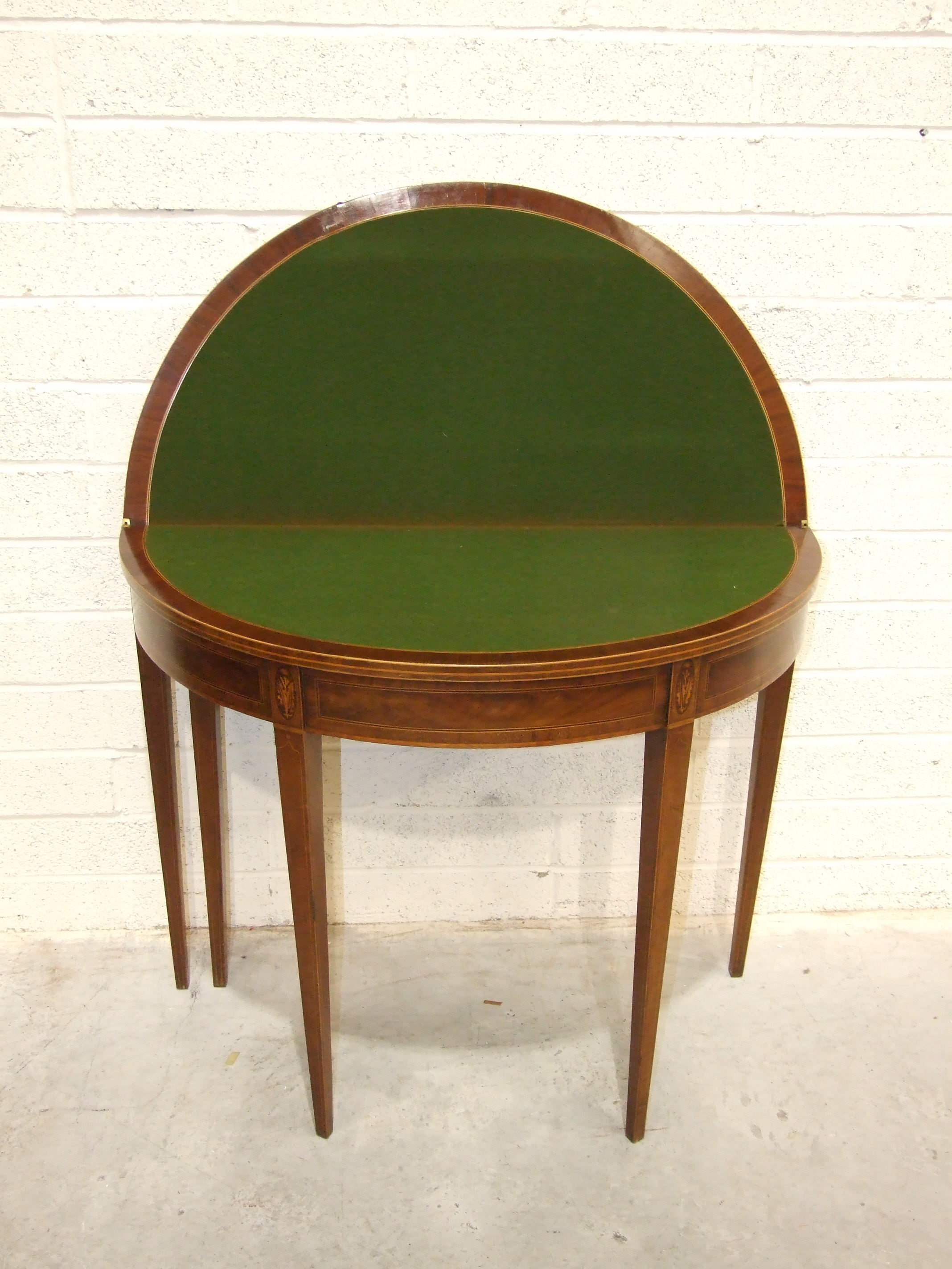 Lot 63 - A Georgian mahogany inlaid fold-over card table, the circular top on square tapered legs, 92cm