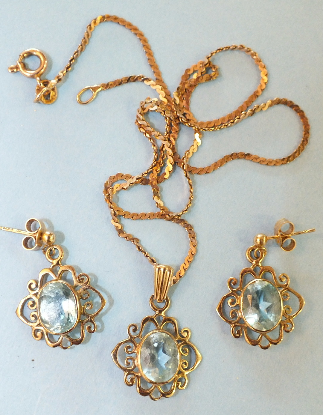 Lot 176 - A blue topaz pendant set oval topaz, in 9ct gold scroll mount, on 9ct gold neck chain, with matching