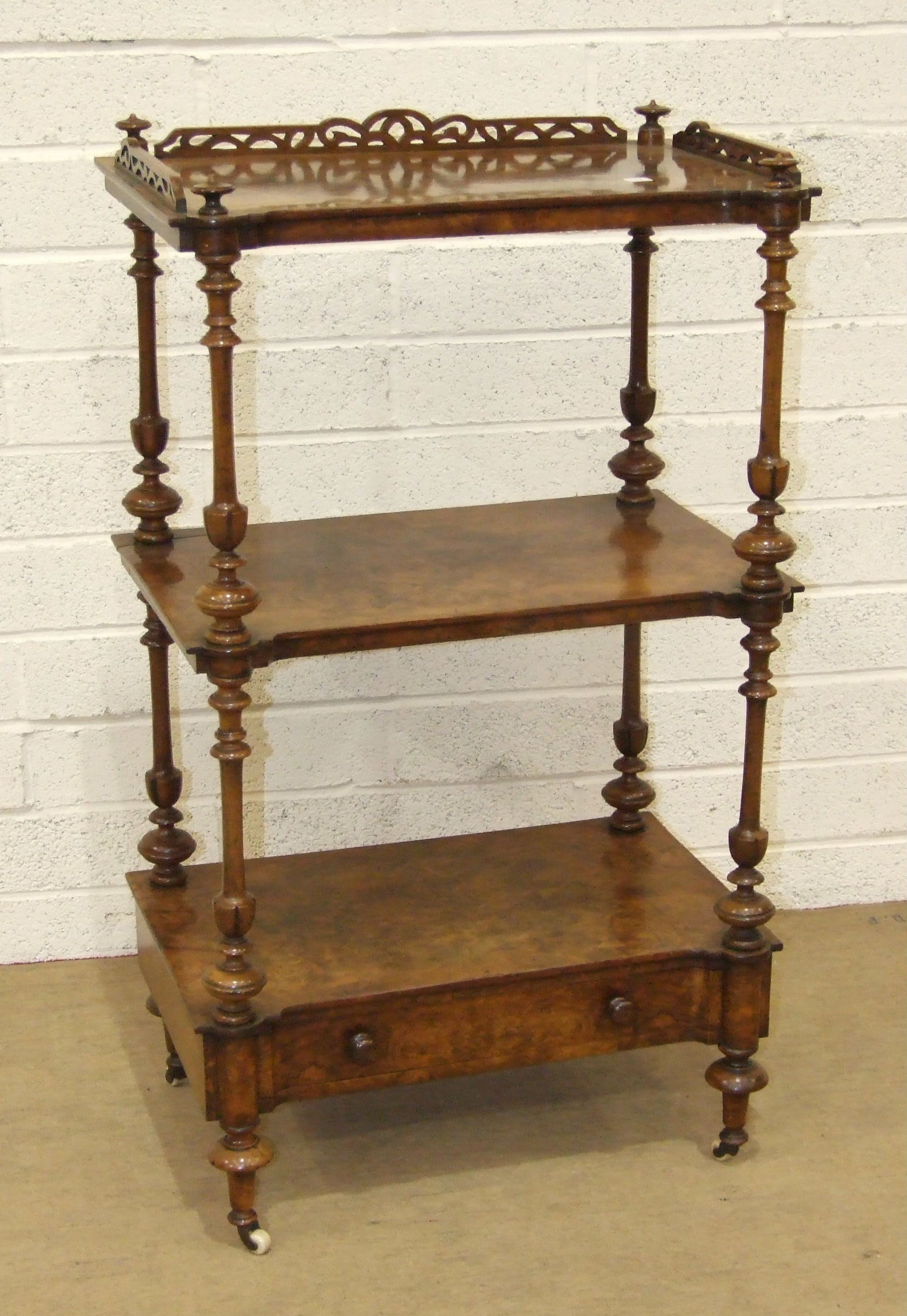 Lot 55 - A Victorian burr walnut three-tier whatnot, the galleried top and tiers separated by turned columns,