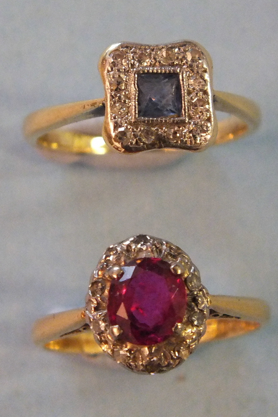Lot 208 - A ruby and diamond cluster ring, claw set an oval ruby within a surround of ten 8/8 cut diamonds