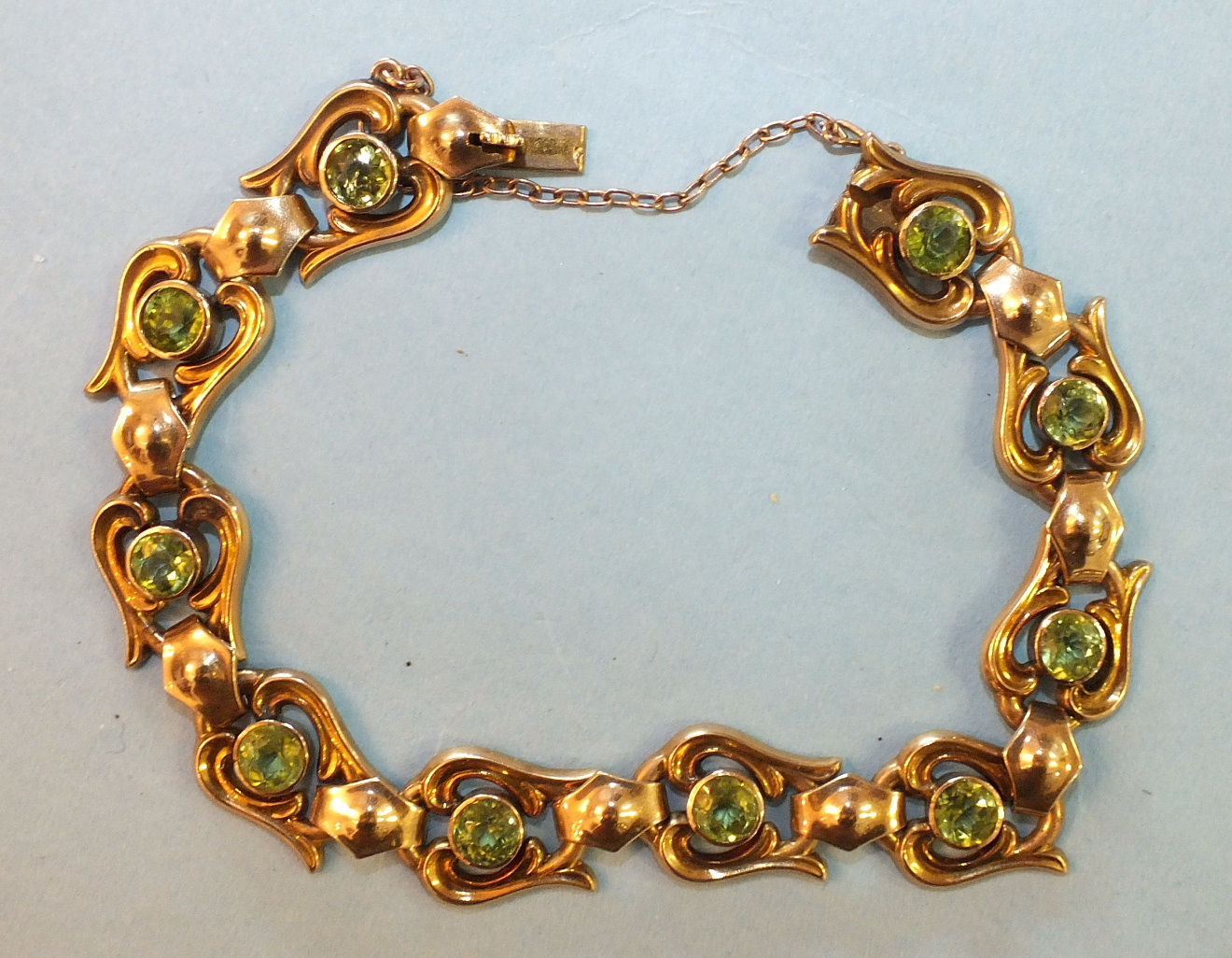 Lot 188 - A 9ct gold bracelet of ten lyre-shaped motifs, each collet-set a round-cut peridot, with concealed