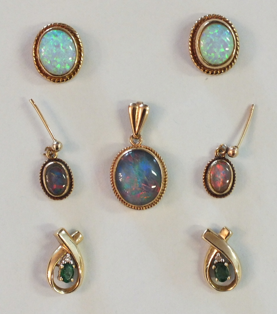Lot 210 - A pair of opal earrings with yellow metal mounts, a pair of black opal doublet earrings and matching