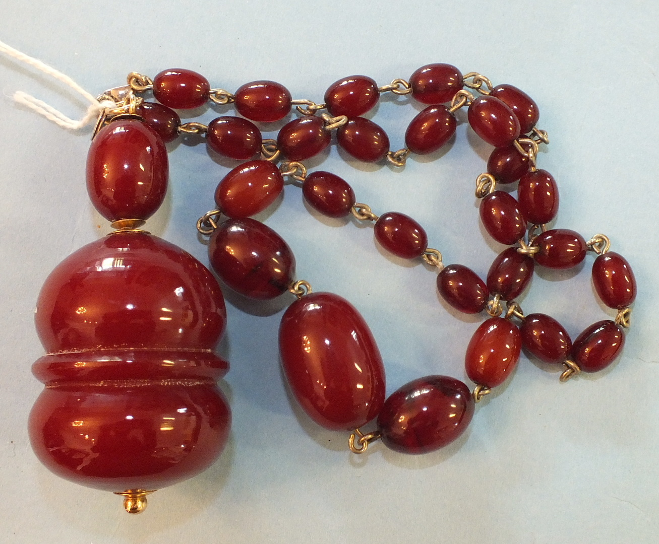 Lot 189 - A very large cherry red Bakelite amber pendant of baluster form, with yellow metal mounts and a