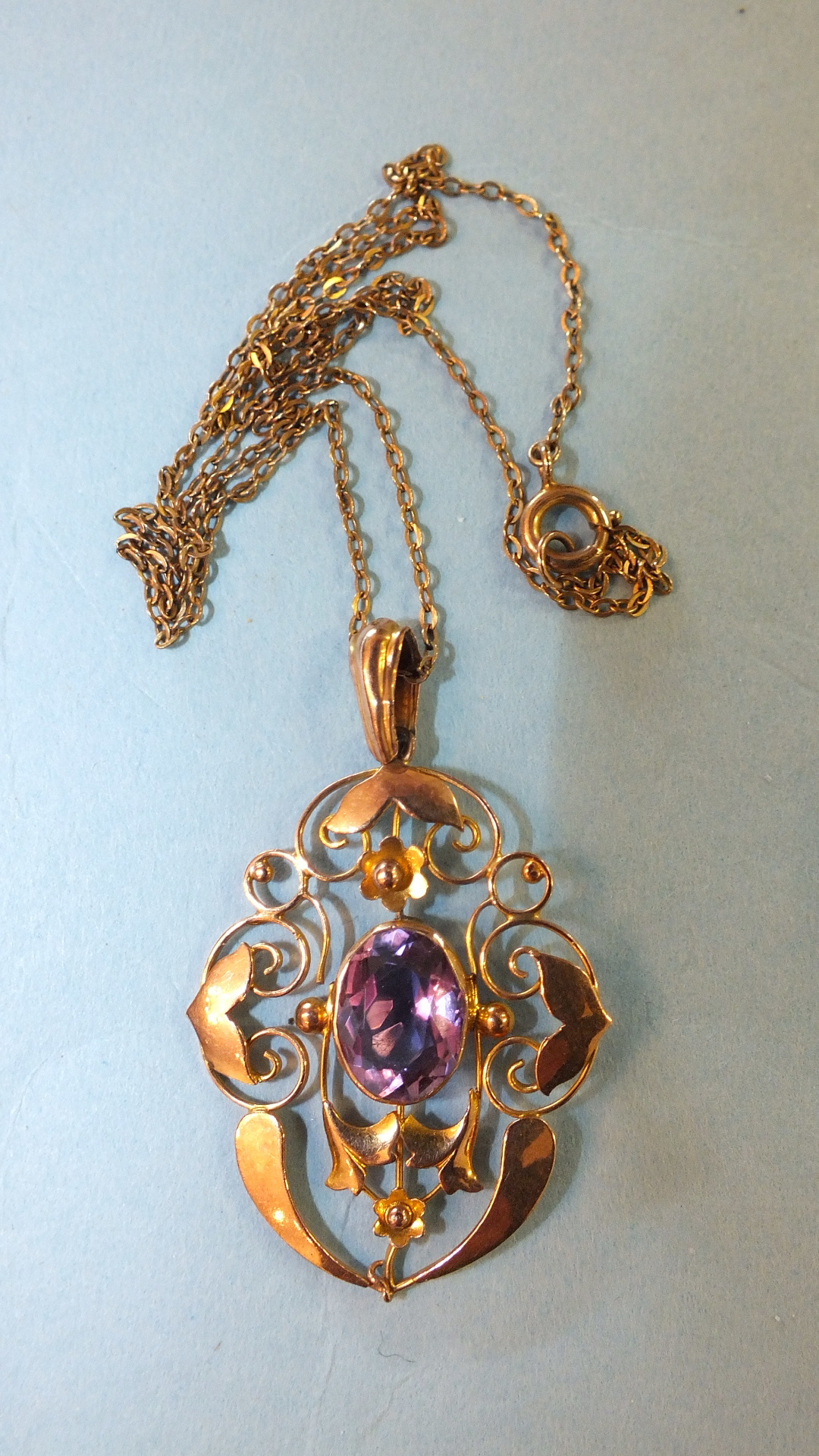 Lot 201 - An Edwardian 9ct gold open-work pendant set amethyst, on trace chain, 3.5g.