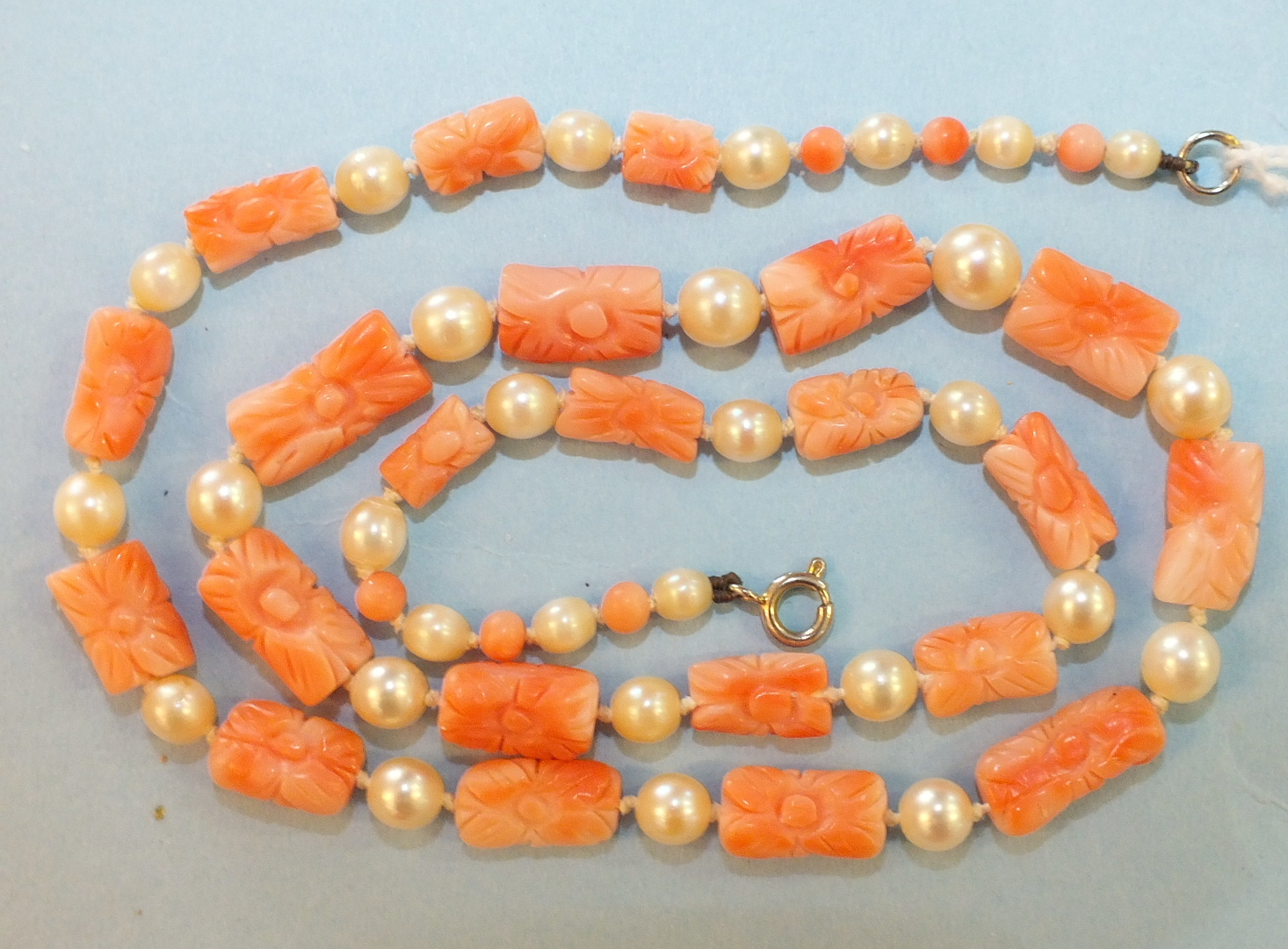 Lot 183 - A necklace of alternate carved pink coral batons and cultured pearls, 50cm.