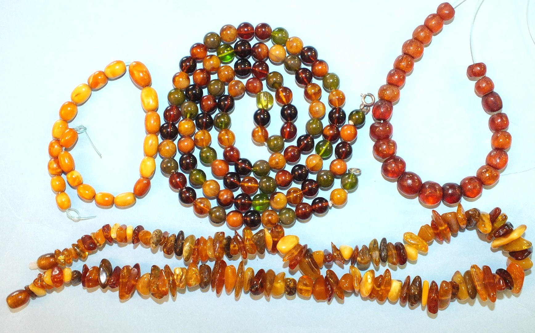 Lot 182 - A string of small multi-coloured amber-type beads, a string of amber chips and a quantity of small