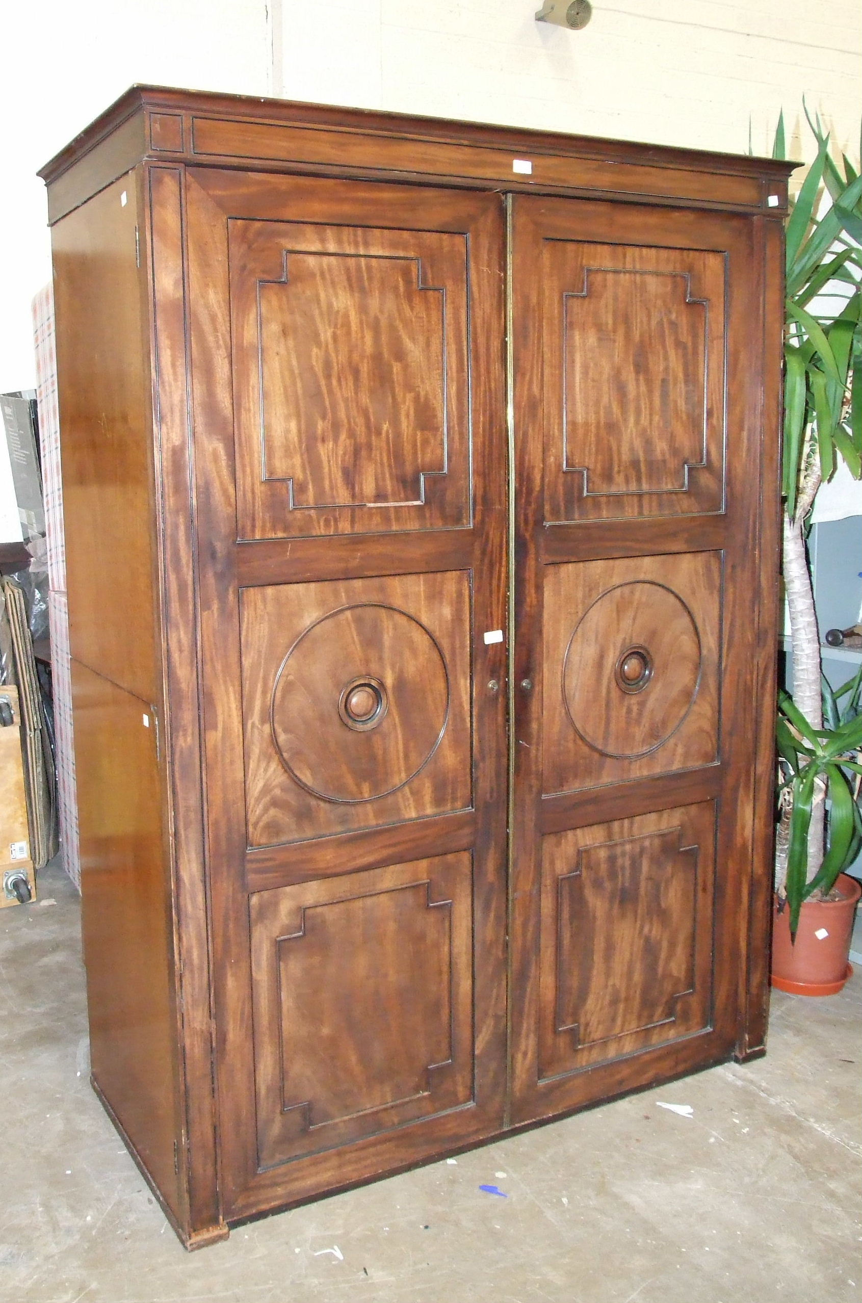 Lot 80 - A George IV mahogany two-door wardrobe press, the cornice above a pair of panelled doors,