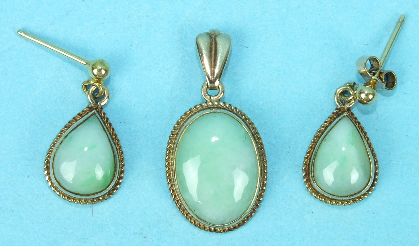 Lot 169 - An oval jade pendant in 9ct gold rope-twist mount and a pair of matching earrings of teardrop
