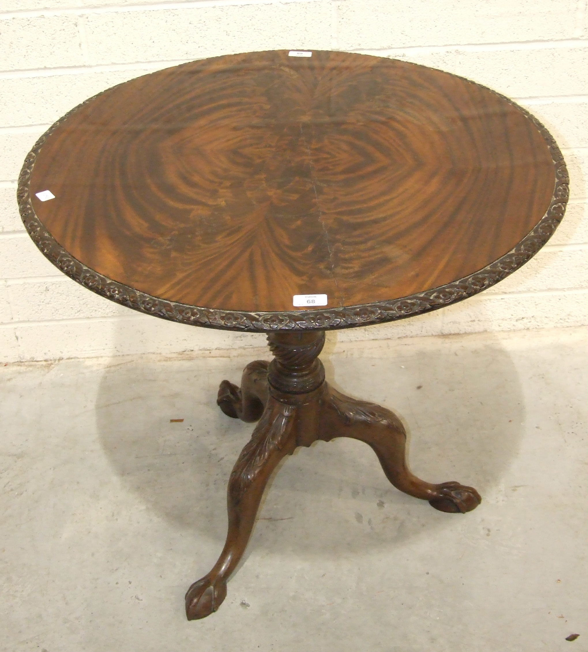 Lot 68 - An 18th century mahogany tripod table stem, with leaf-carved legs, claw feet and later circular top,