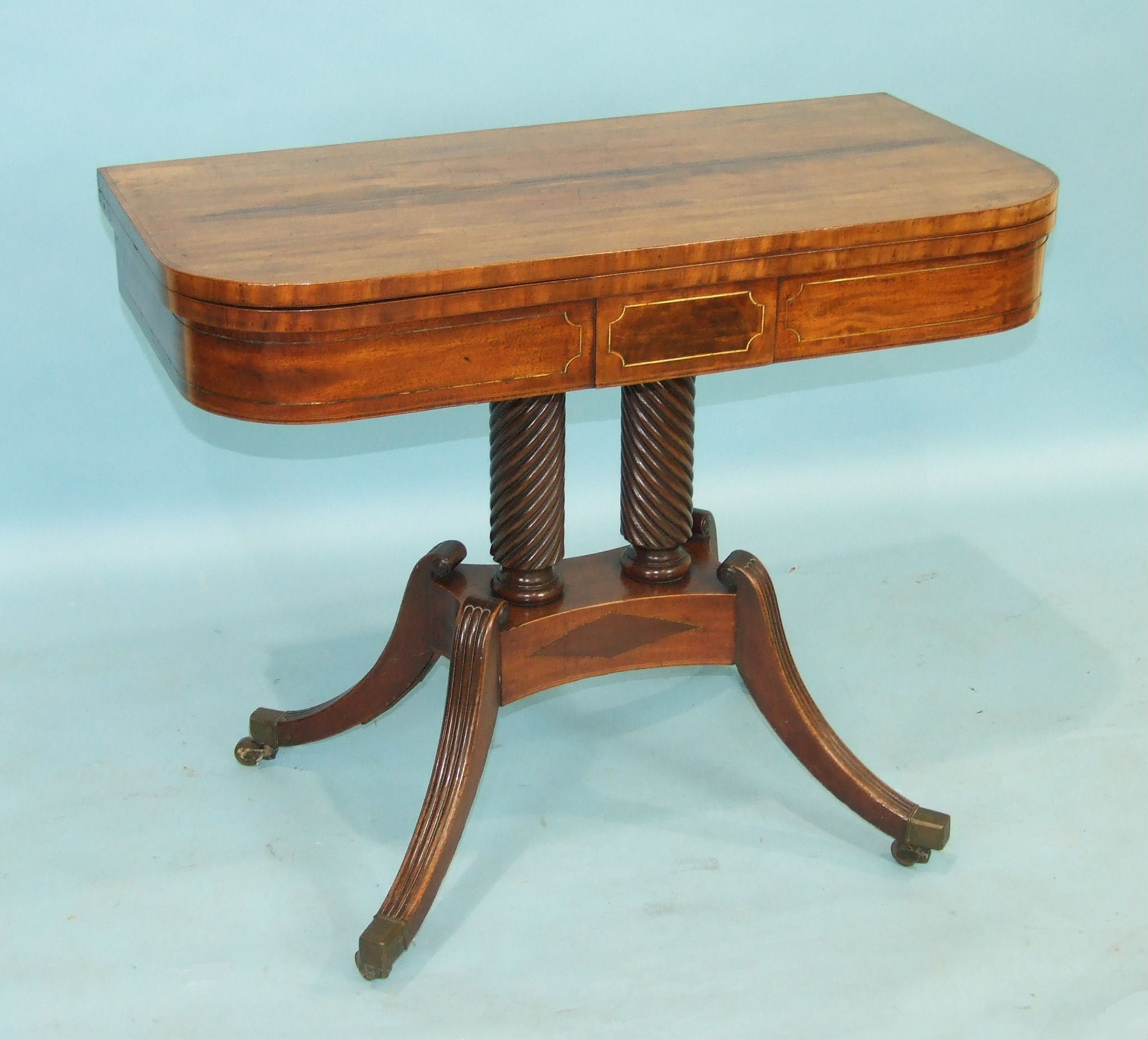 Lot 76 - A Regency mahogany fold-over card table, the baize-lined top above a brass-inlaid frieze, raised