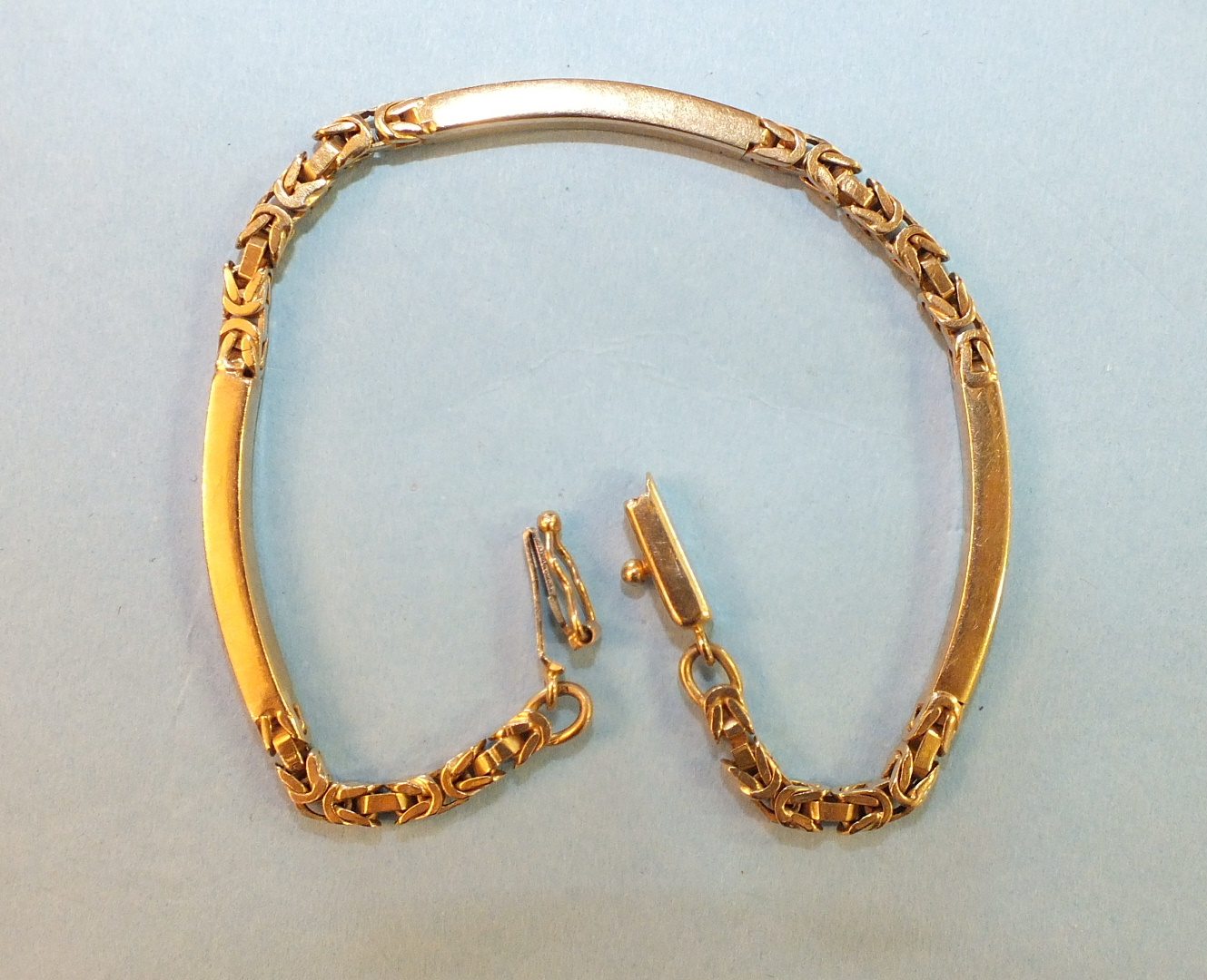 Lot 215 - A 9ct gold bracelet of curved batons and fancy links, 9g.