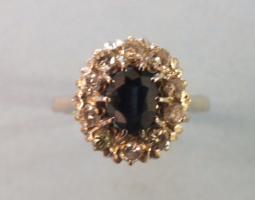 Lot 224 - A sapphire and diamond cluster ring, claw set an oval sapphire within a border of ten brilliant
