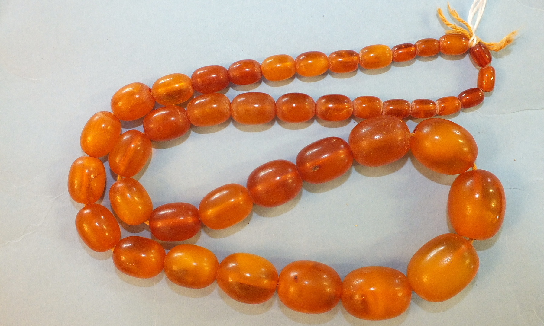 Lot 197 - An amber necklace of forty-one graduated butterscotch amber ovoid beads, 2.5cm - 0.8cm long, 63.2g.