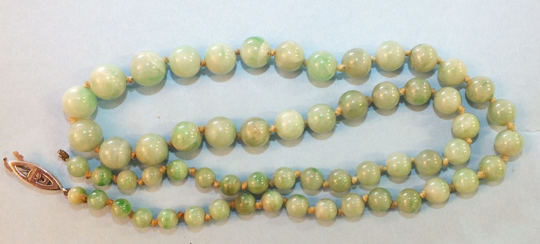 Lot 200 - A jade necklace of sixty graduated spherical beads, graduating from 5mm to 9.5mm approximately, 54cm