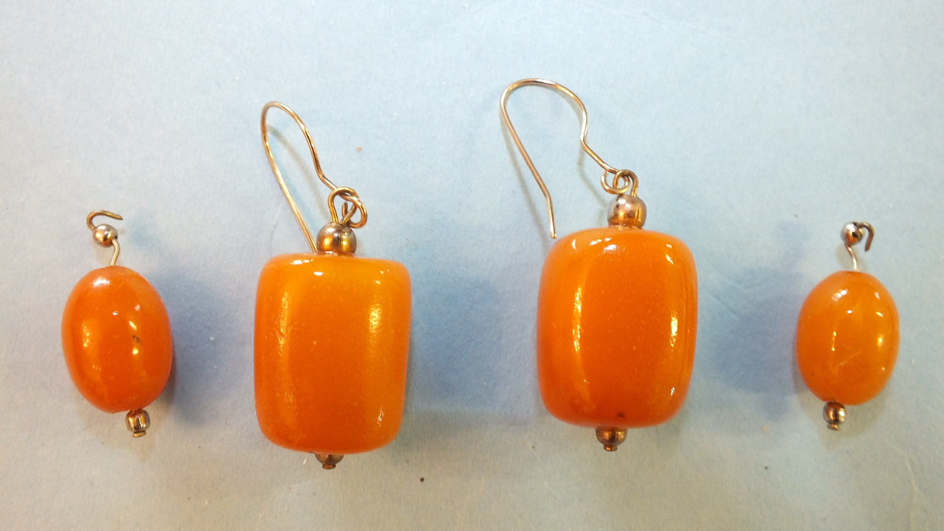 Lot 192 - A pair of amber drop earrings and a pair of smaller amber beads on metal mounts, total wt 10g.