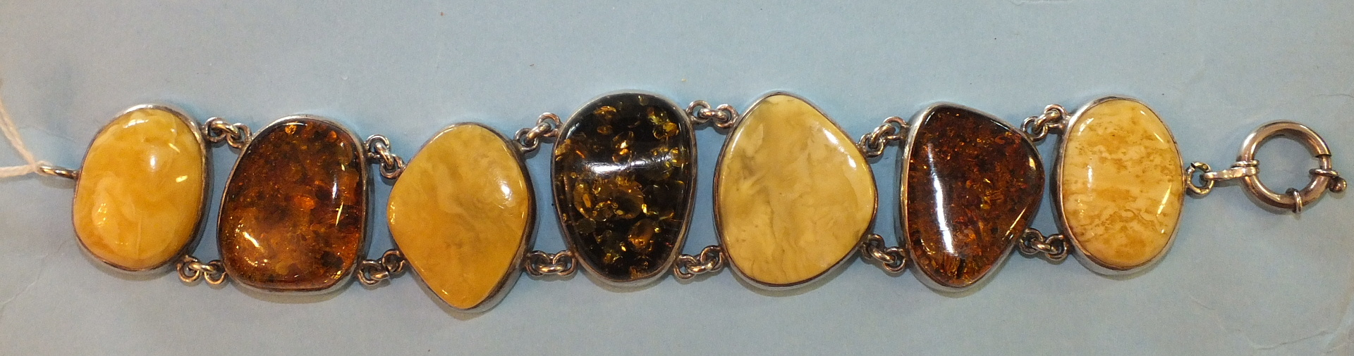 Lot 186 - A bracelet of seven amber plaques of irregular shape set in silver, marked '925', with bolt-ring