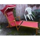 A reclining deck chair with canopy and foot rest