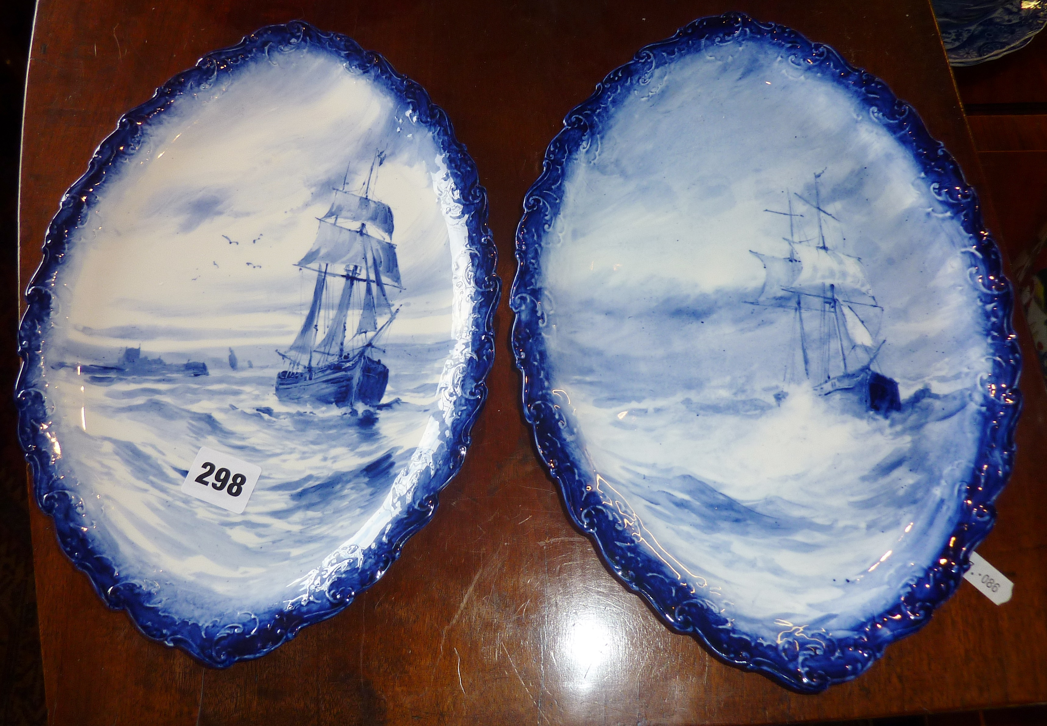 Lot 298 - Pair of Royal Crown Derby blue and white shaped plaques with sailing vessels decoration