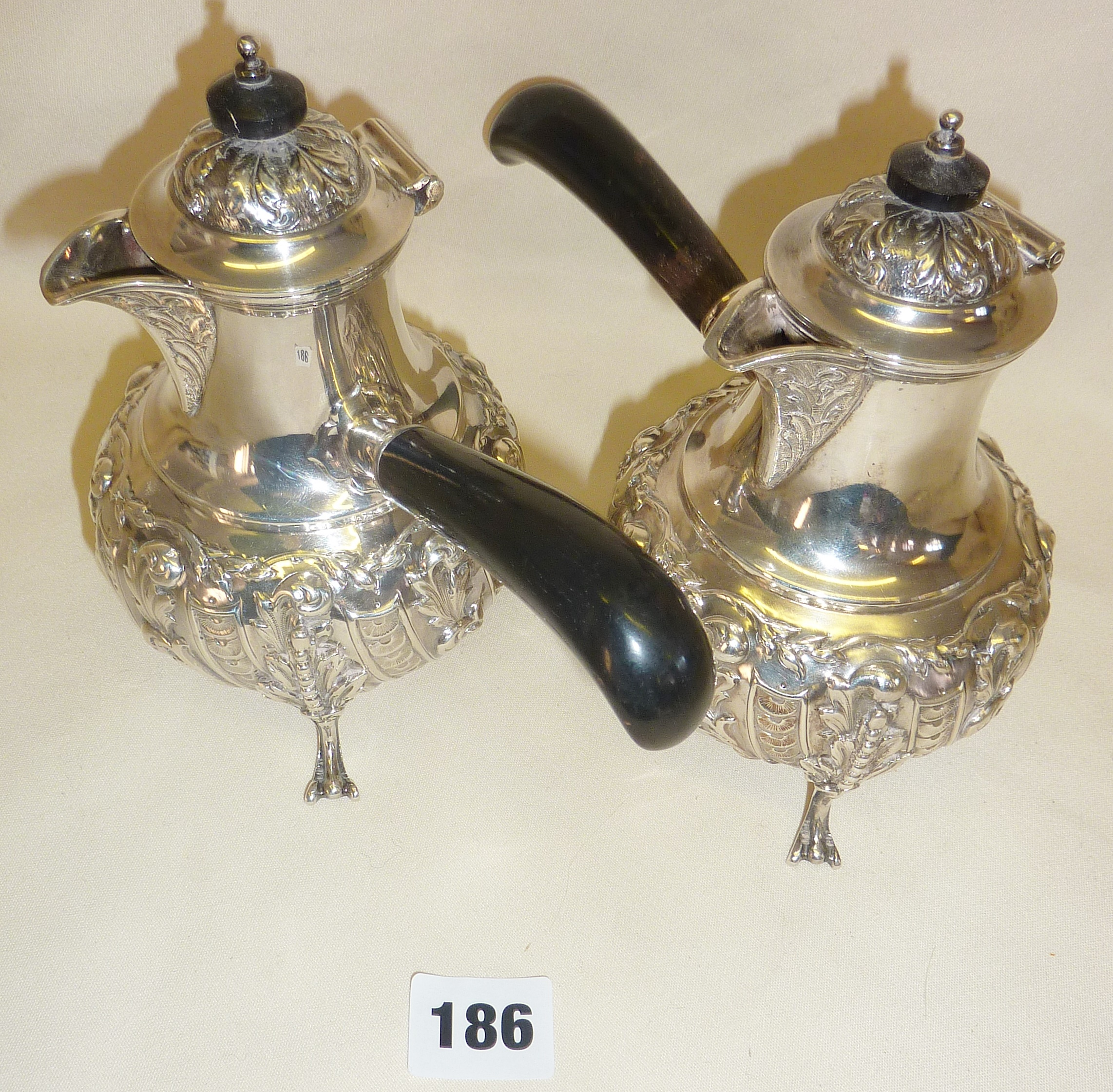 Pair of finely chased repoussé silver chocolate pots with ebonised handles, hallmarked for London