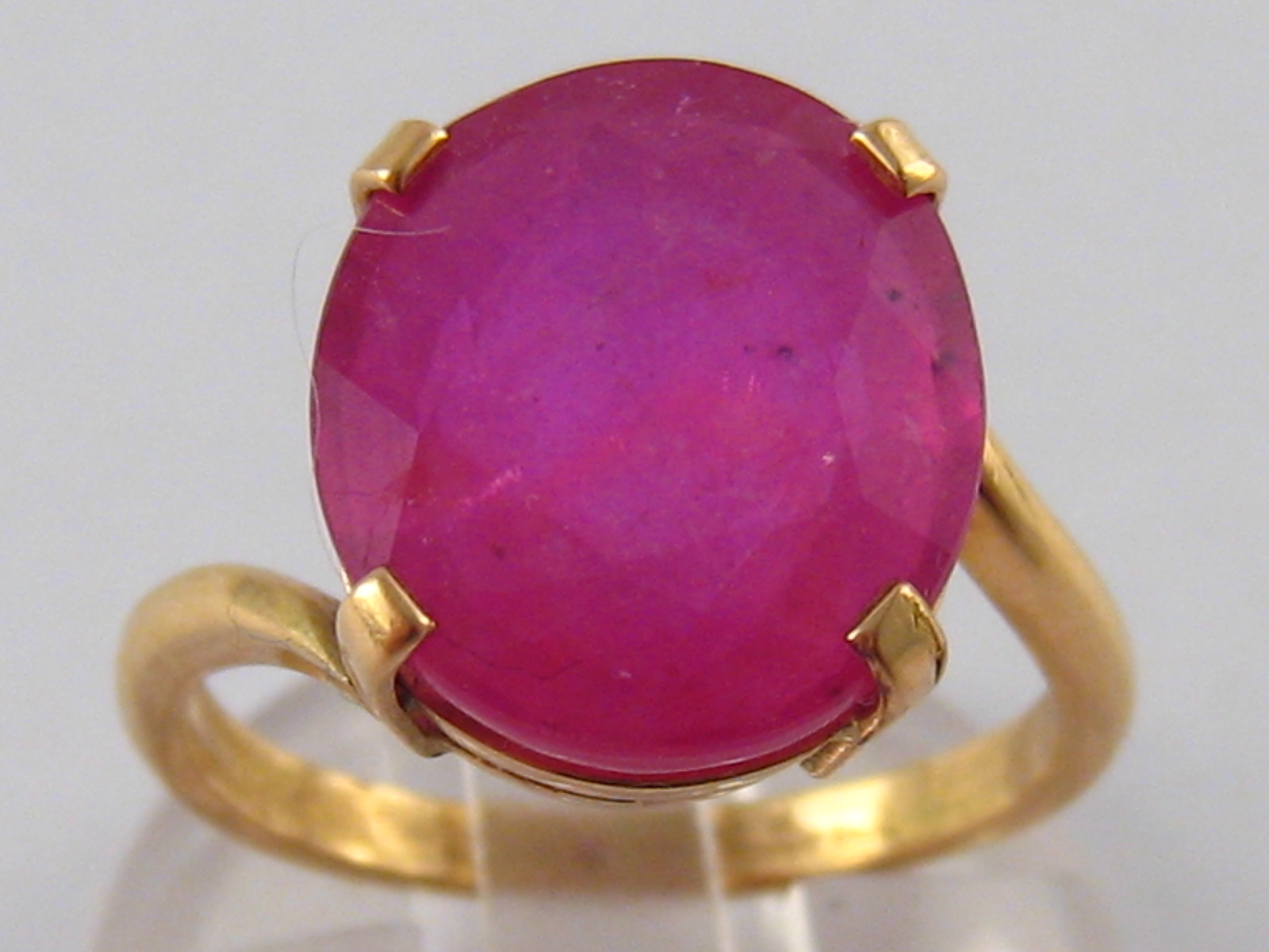 A yellow metal (tests 18 carat gold) ruby ring, the colour enhanced ruby measuring approx 14 x 12mm,
