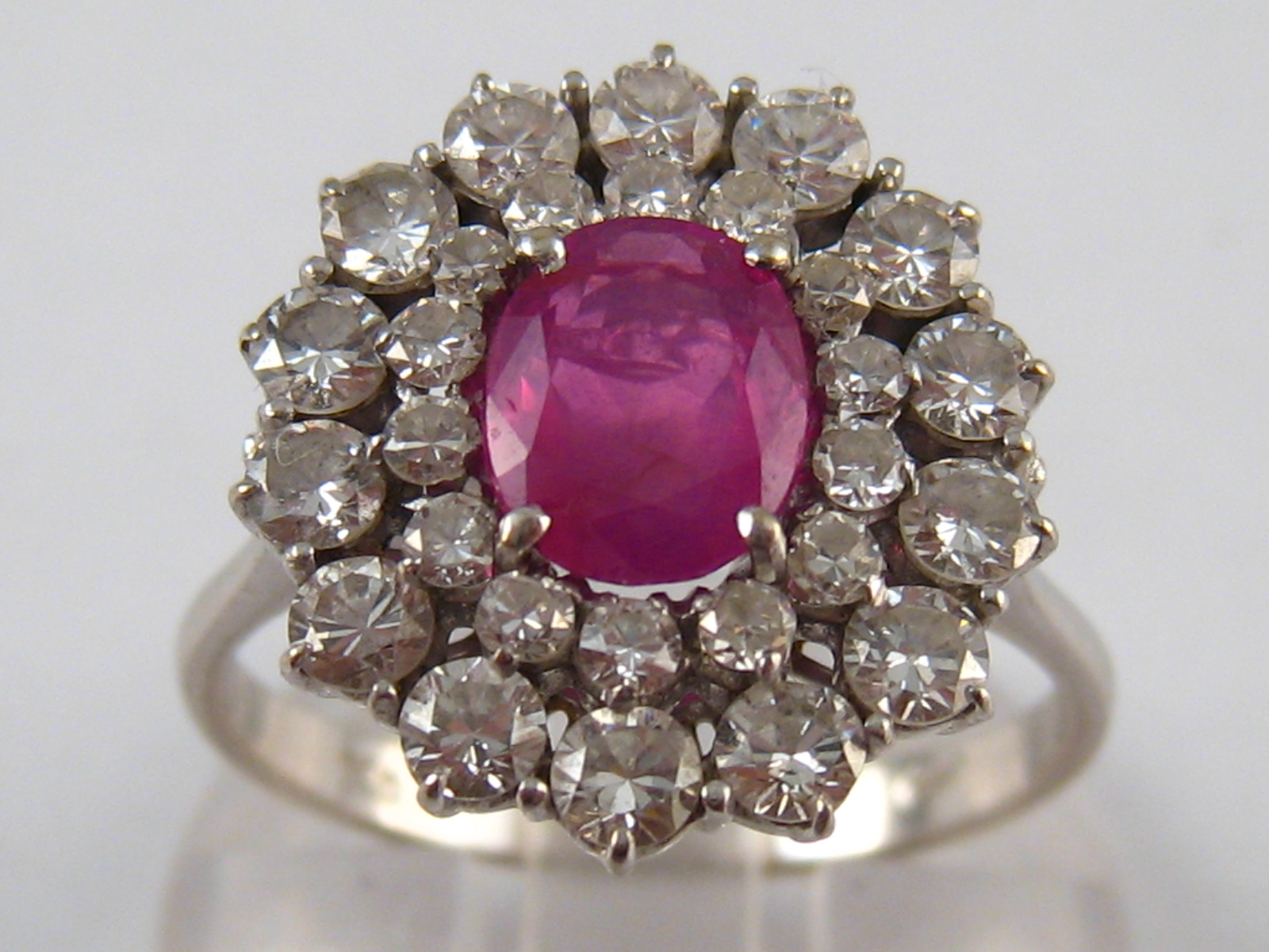 A white metal (tests 18 carat gold) diamond and ruby ring, the ruby measuring approx. 7.