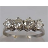 A white metal (tests 18 carat gold) four stone diamond ring, estimated total diamond content 0.75-0.
