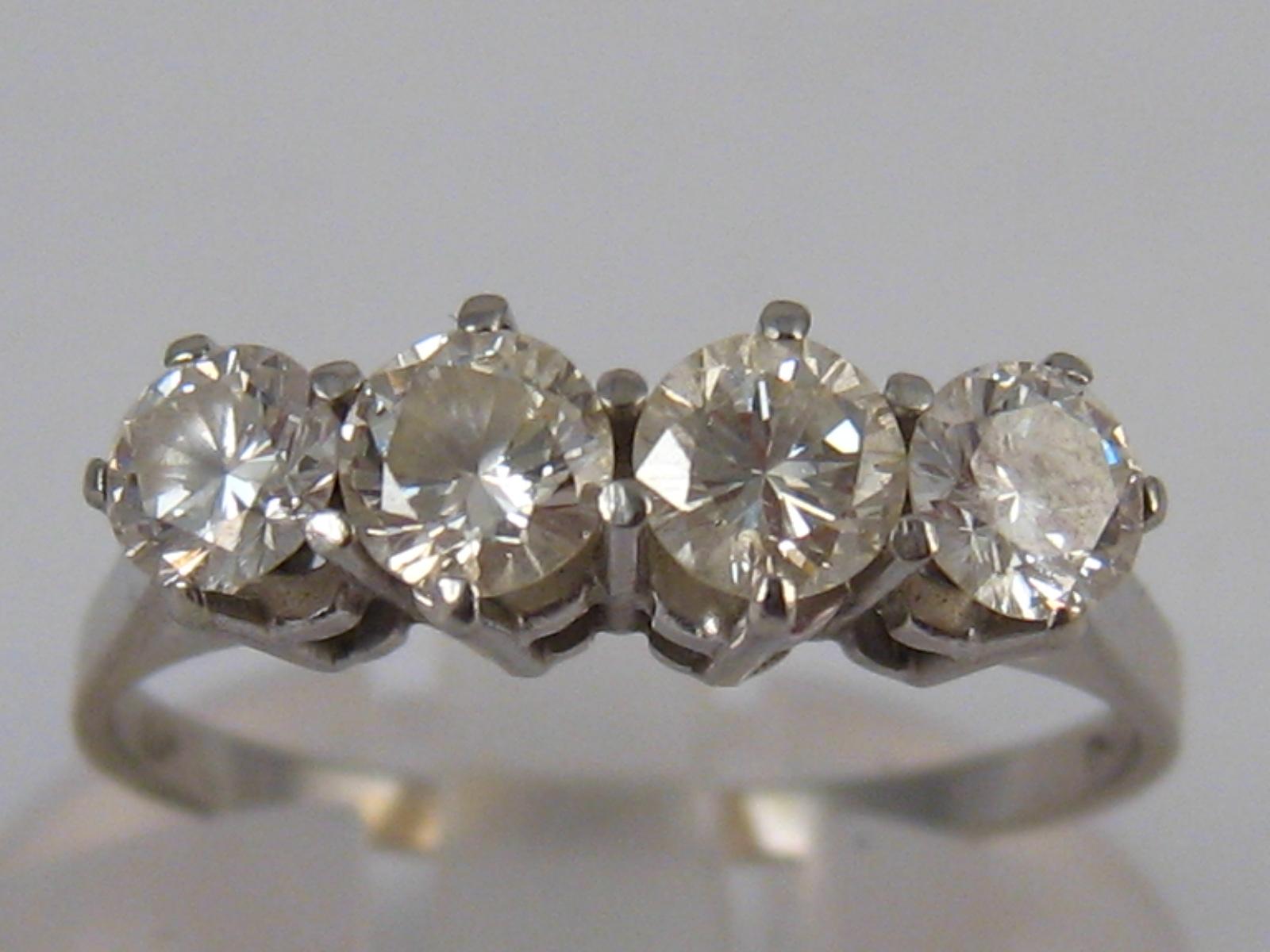 A white metal (tests 18 carat gold) four stone diamond ring, estimated total diamond content 0.75-0.