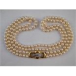 A two row cultured pearl necklace with a yellow metal (tests 18 carat gold) diamond set clasp,