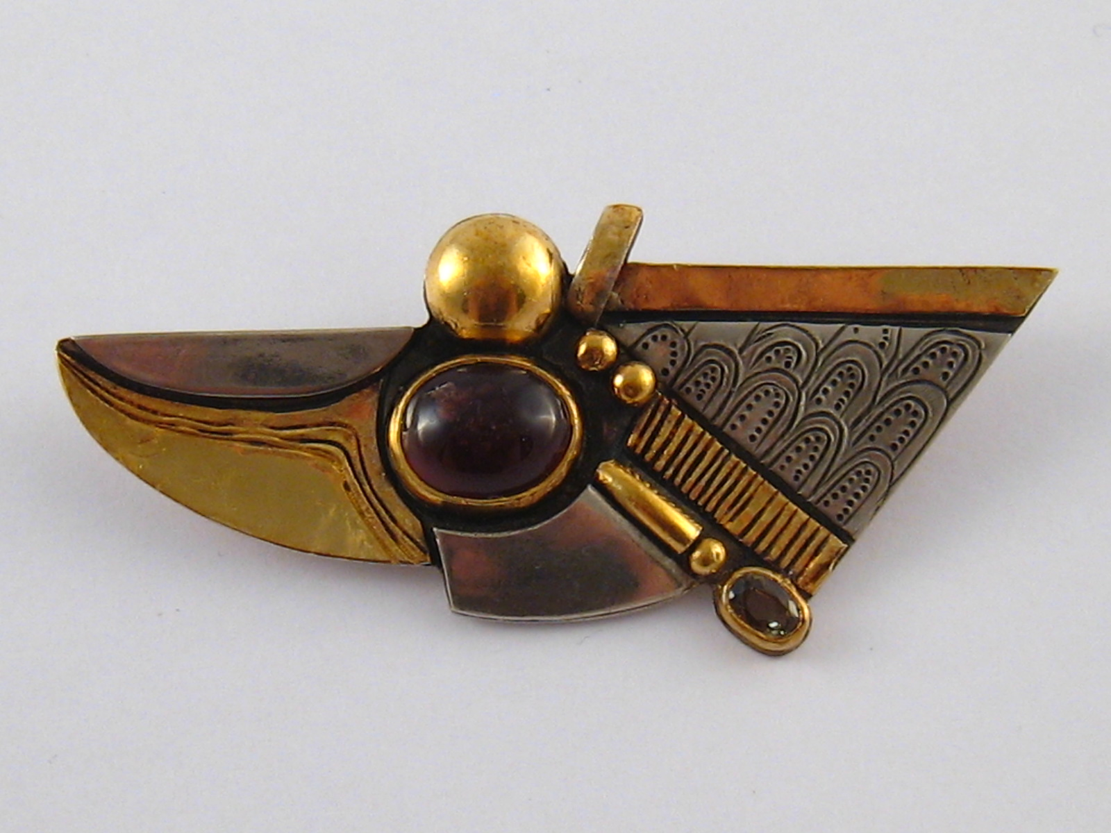 Lot 143 - A gilt and white metal (tests silver) garnet brooch, signed HB, garnet approx 12 x 10mm,