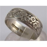 A platinum band ring with chased and engraved floral decoration, approx 6mm wide, size M, 5.5 gms.