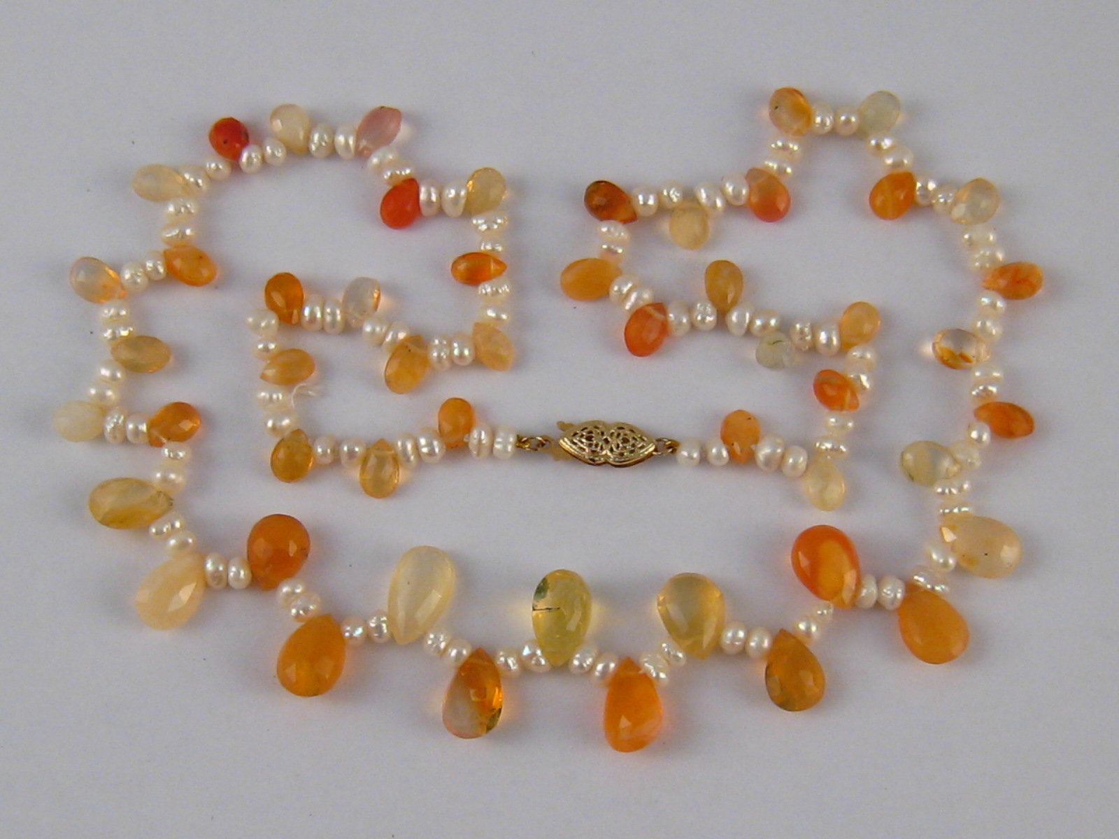 Lot 98 - A cultured pearl, fire opal and citrine necklace with a yellow metal (tests 14 carat gold) clasp,