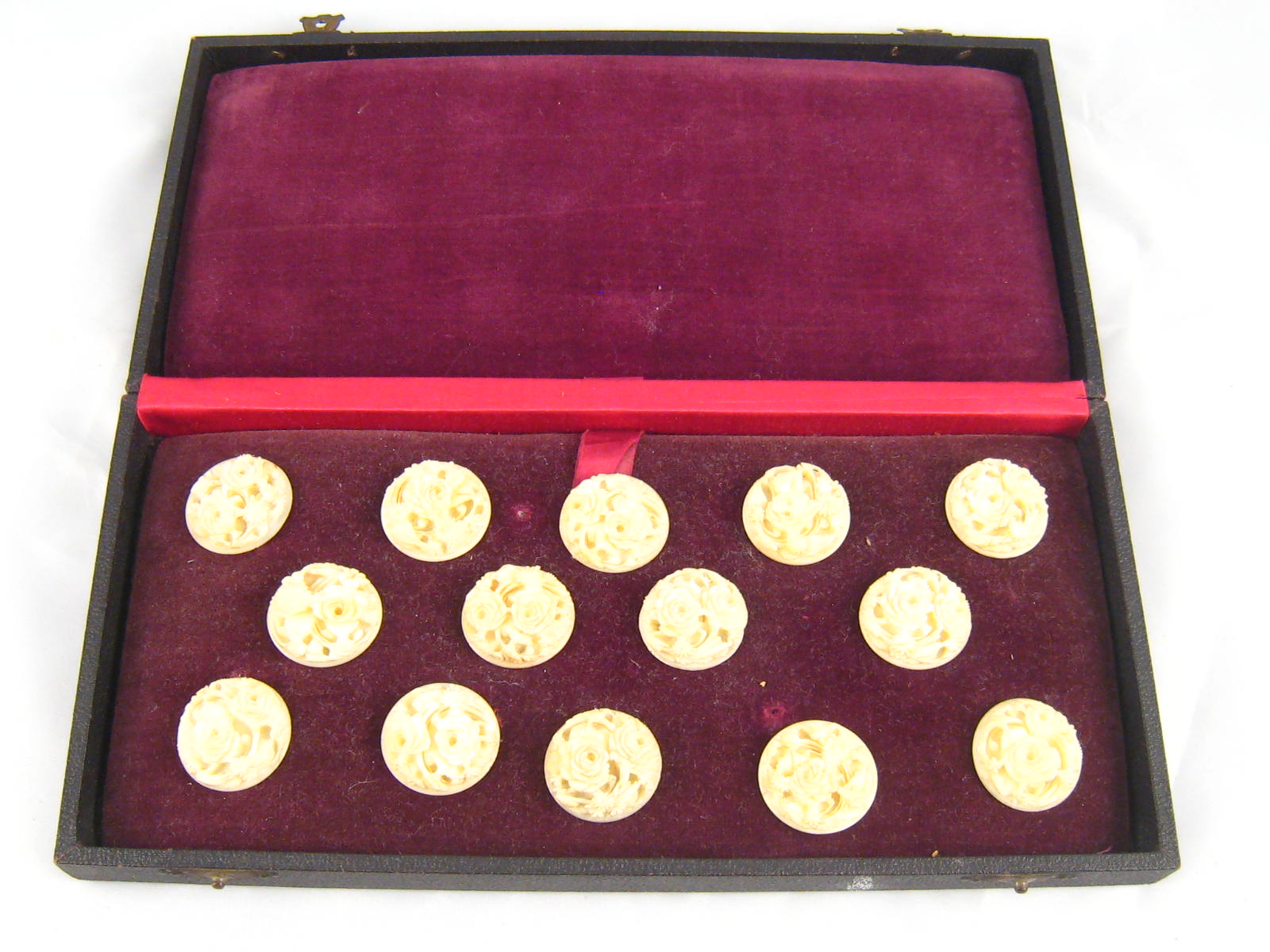 Lot 401 - A set of twelve carved ivory buttons with screwed stud fixings in fitted box, circa 1920.