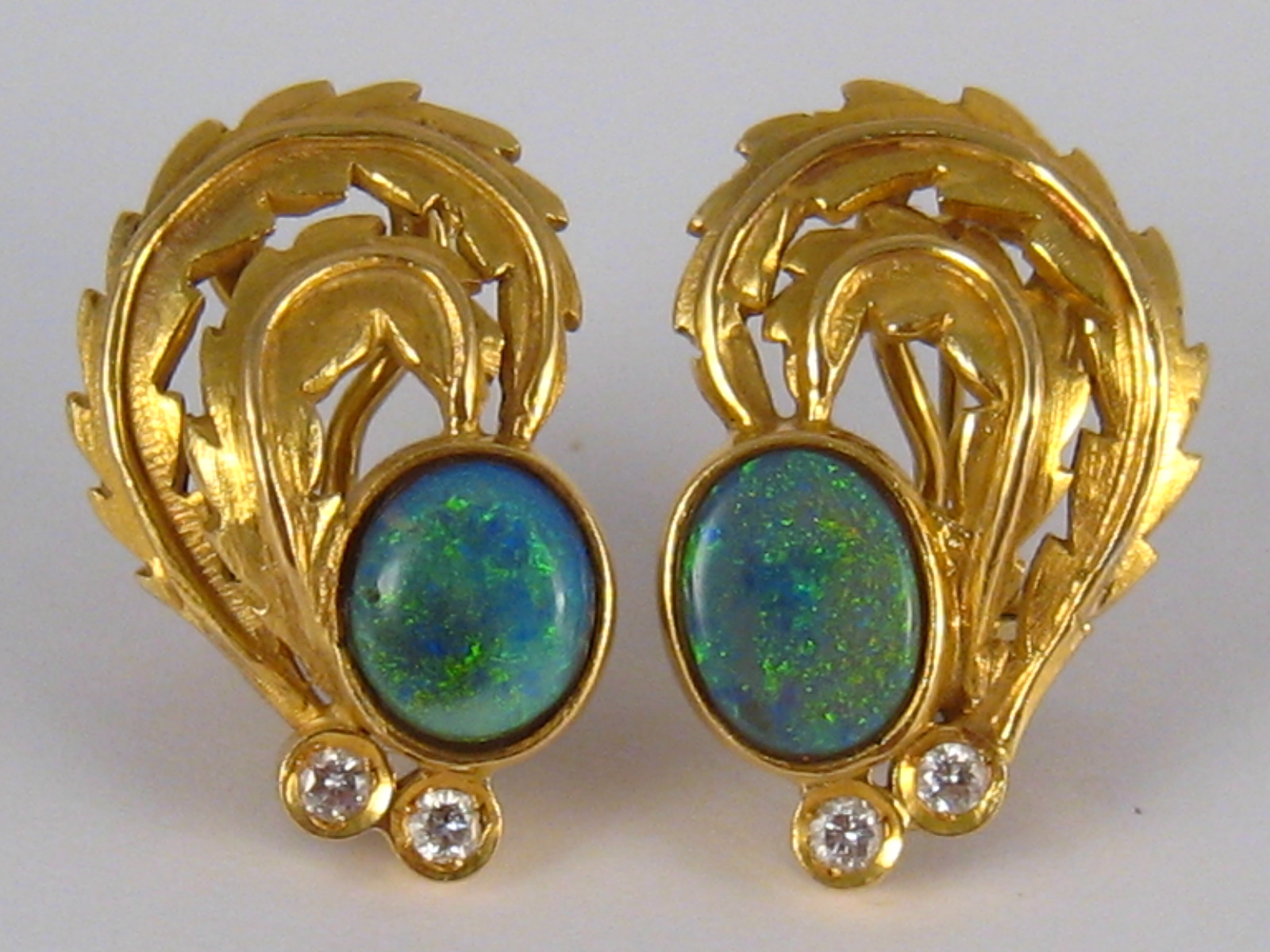Lot 77 - A pair of yellow metal (tests 18 carat gold) diamond and opal earrings. Opals approx. 9x7.