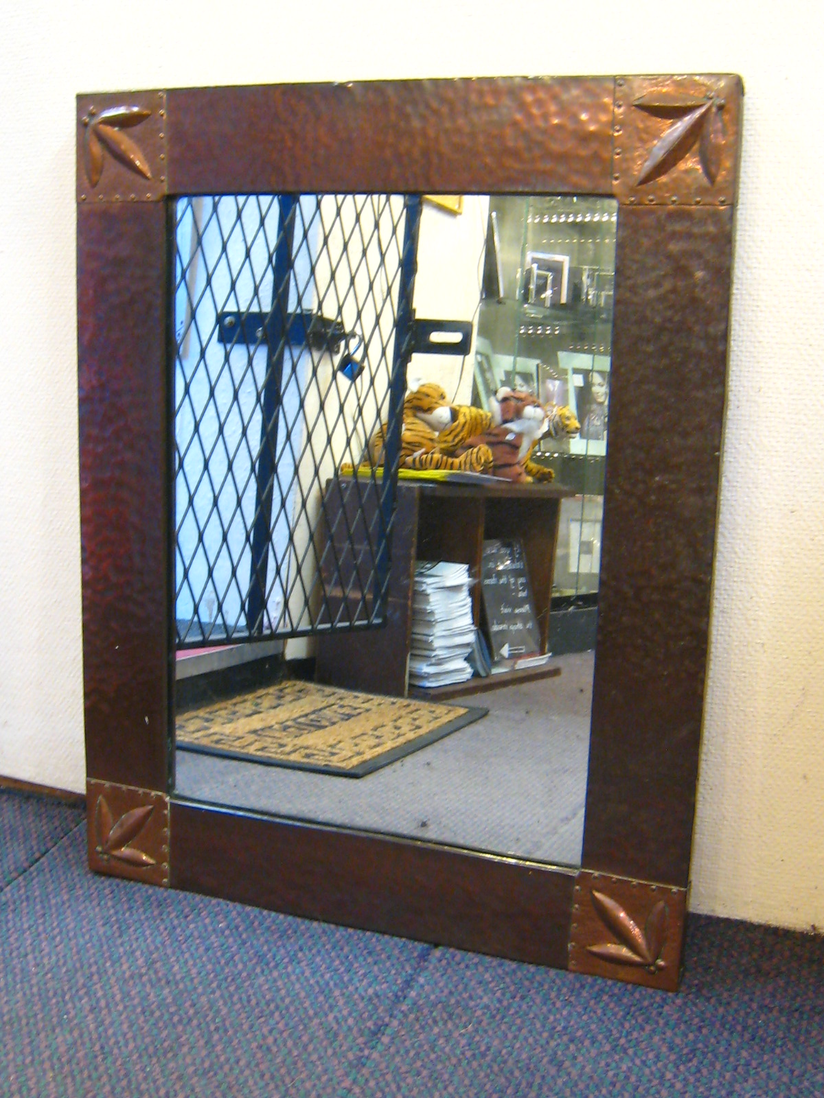 Lot 440 - A copper framed Arts and Crafts mirror with hammered finish ,