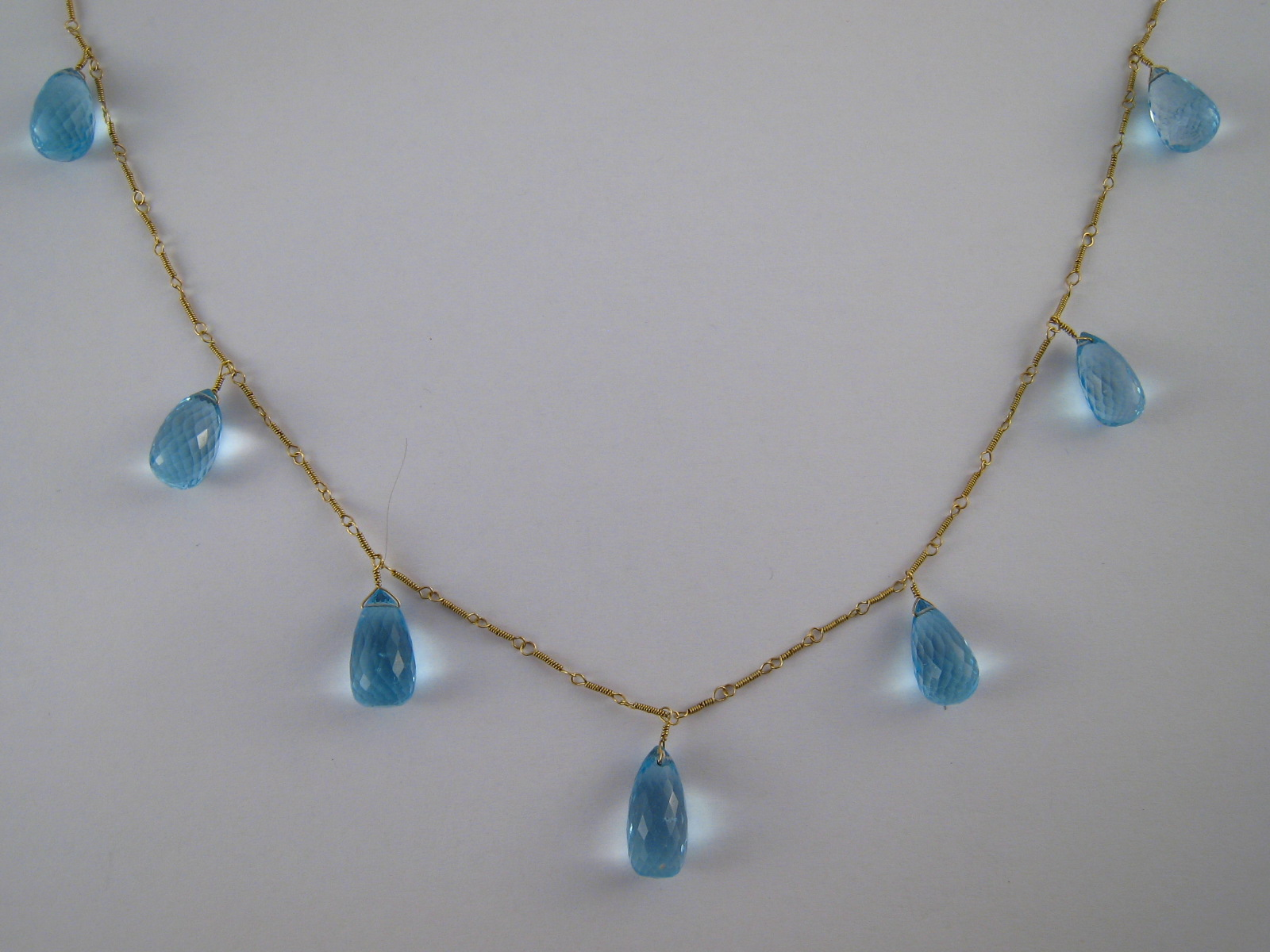 A yellow metal  (tests 18 carat gold) blue topaz necklace, each topaz approx 15 x 8mm,