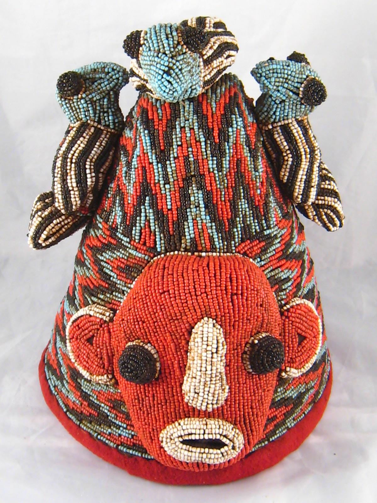 Lot 426 - Tribal Art . A Yoruba beaded hat adorned with three birds, Nigeria. Ht. 33cm.