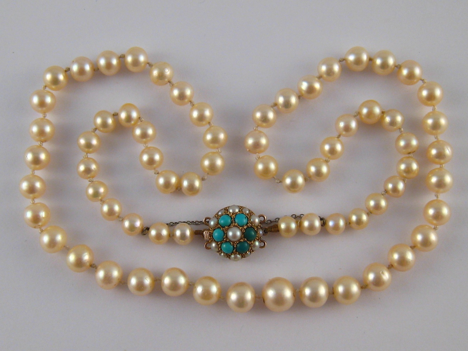 A graduated cultured pearl necklace with a yellow metal (tests 9 carat gold) turquoise and seed