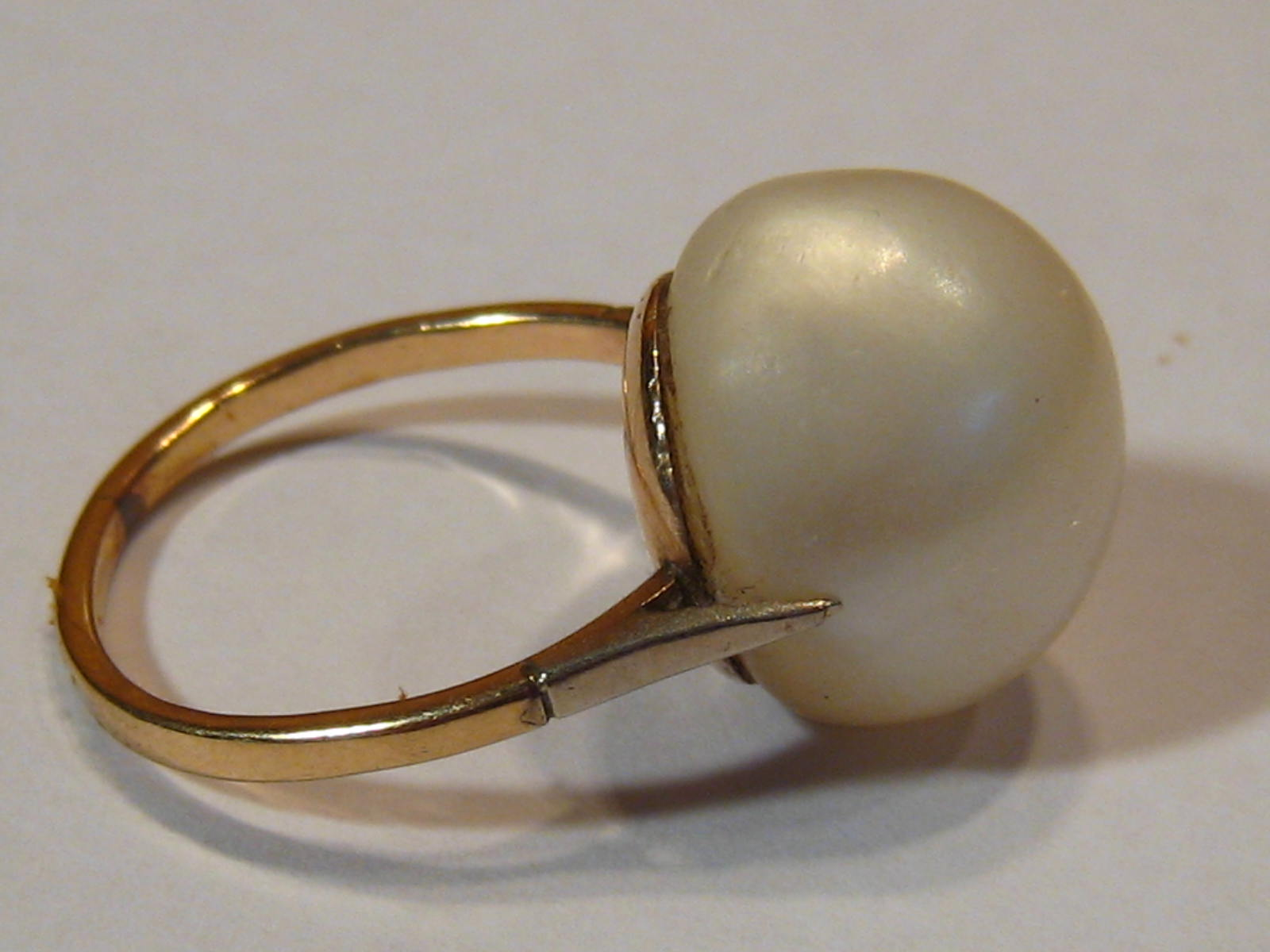 Lot 142 - A yellow metal (tests 9 carat gold) untested baroque pearl ring, pearl approx 14mm long,