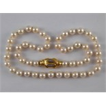 A cultured pearl necklace with a yellow metal (tests 18 carat gold) and diamond clasp,